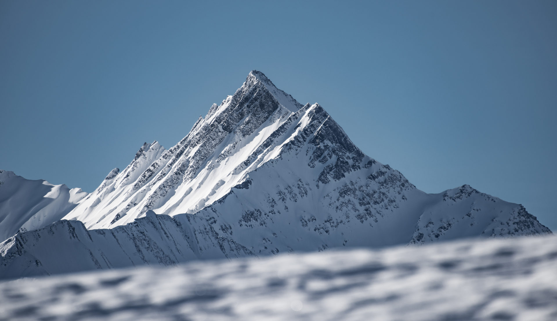 verschneite Bergspitze in der Surselva mit blauem Himmel und Sonne